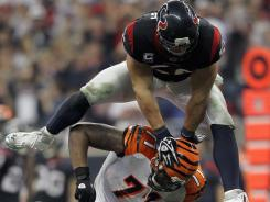 The Texans' Brian Cushing hurdles over a Cincinnati Bengals player during the first half in Houston.