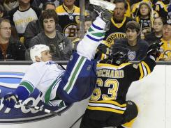 Boston Bruins left wing Brad Marchand upends Vancouver Canucks defenseman Sami Salo during the second period Saturday.
