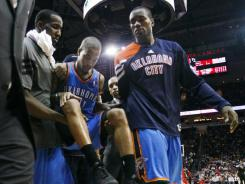 Oklahoma City guard Eric Maynor, middle, is carried off the court after tearing a knee ligament in the Thunder's 98-95 victory Saturday at the Houston Rockets. Maynor is done for the season.