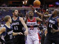 Wizards power forward Trevor Booker (35) battles for a loose ball with Timberwolves teammates Luke Ridnour, Kevin Love and Anthony Tolliver during the first half in Washington. Love led Minnesota's rout with 20 points and 16 rebounds.