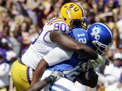 LSU defensive tackle Michael Brockers stops Kentucky quarterback Morgan Newton in the first quarter of an NCAA college football game in Baton Rouge, La., Saturday, Oct. 1, 2011.