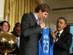 Dallas Mavericks star Dirk Nowitzki presents a team jersey Monday to President Obama, who welcomed the defending NBA champions to the White House.