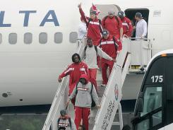 The Alabama football team arrives at Tuscaloosa Regional Airport in Tuscaloosa, Ala., Tuesday after winning the BCS national title Monday night.