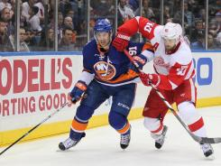 John Tavares (91), seen here fighting for the puck with Detroit's Henrik Zetterberg, left in the second period after being hit in the head with a puck. He returned to the game several minutes later and finished the game with a goal and two assists.