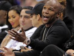 Floyd Mayweather Jr. talks to a referee as he watches a Los Angeles Clippers game in December.
