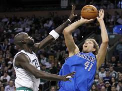 Mavericks forward Dirk Nowitzki (41) fades away for a shot while guarded by Celtics forward Kevin Garnett (5) during the second quarter at TD Banknorth Garden in Boston.