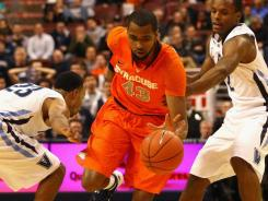 Syracuse's James Southerland  splits Villanova's Dominic Cheek (23) and Maalik Wayns at the Wells Fargo Center in Philadelphia,