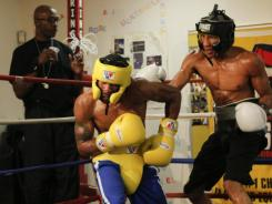 Lamont Peterson (yellow) spars before his fight with Amir Khan under the watchful eye of his trainer, Barry Hunter. Hunter issued a statement bashing the protest Khan has lodged over Peterson's split decision victory.