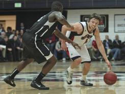 Saint Mary's guard Matthew Dellavedova, right, here driving against Gonzaga guard Gary Bell, connected on five three-pointers en route to 26 points.