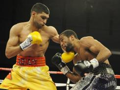 Amir Khan, left, lost his WBA and IBF belts to Lamont Peterson on a split decision after being docked two points for pushing in the Dec. 10 fight.