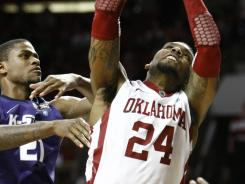 Oklahoma forward Romero Osby slams home a basket in front of Kansas State's Jordan Henriquez  during the Sooners' 82-73 win.