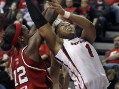 Rutgers' Khadijah Rushdan takes a shot past Louisville's Shawnta' Dyer during the first half of an NCAA college basketball game in Piscataway, N.J., Saturday, Jan. 14, 2012.