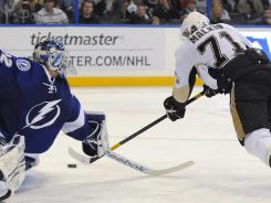Penguins center Evgeni Malkin shoots past Lightning goalie Mathieu Garon to score his second goal of the third period Sunday.