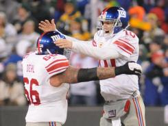 Eli Manning (10) celebrates his second-quarter touchdown pass with guard David Diehl. Manning threw for 330 yards and three touchdowns.