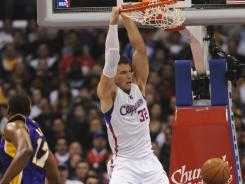 Clippers power forward Blake Griffin (32) throws down a slam dunk past Lakers center Andrew Bynum (17) during first-half action at Staples Center.
