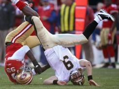 Quarterback Drew Brees, here getting sacked by the 49ers' Aldon Smith on Saturday, and the Saints had their nine-game winning streak end with a heartbreaking defeat.