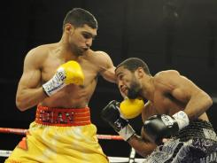 Knowing a rematch has been ordered, Amir Khan, left, will get another shot at Lamont Peterson, right.