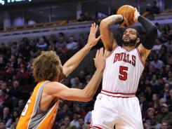 Bulls power forward Carlos Boozer, right, shoots over ball Suns center Robin Lopez in the second quarter on Tuesday. Boozer had a season-high 31 points in Chicago's win.