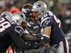 Tackle Gerard Warren, left, and outside linebacker Rob Ninkovich sack the Broncos' Tim Tebow during their divisional playoff game Saturday. New England yielded the second-most passing yards in NFL history.