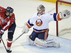New York Islanders goalie Evgeni Nabokov (20) makes a glove save against Capitals center Brooks Laich during the second period in Washington, D.C.