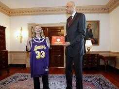 Secretary of State Hillary Clinton showcases the Los Angeles Lakers jersey of Hall of Famer Kareem Abdul-Jabbar, whom she named a cultural ambassador Wednesday for the United States