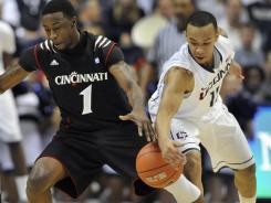 Connecticut's Shabazz Napier, right, steals the ball from Cincinnati's Cashmere Wright (1) in the first half in Storrs, Conn.