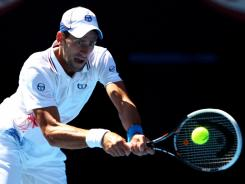 Serbia's Novak Djokovic plays a backhand in his second-round match against Colombia's Santiago Giraldo at Melbourne Park. Djokovic advanced with a straight-set win.