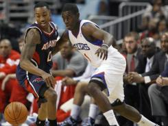 Jrue Holiday, right, had 16 points and 11 assists to help the 76ers rally by Jeff Teague and the Hawks.