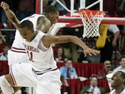 Arkansas' B.J. Young (11) celebrates with teammates Devonta Abron, rear left, and Mardracus Wade (1) after defeating Michigan 66-64 Saturday.