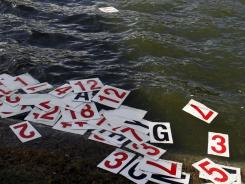 Numbers float in the lake on the 18th hole after high winds blew the scoreboard into the water during the third round of the Humana Challenge in La Quinta, Calif. Play was suspended when the high winds caused damaged to all three courses.