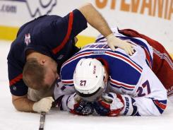 New York Rangers defenseman Ryan McDonagh is examined by a trainer after being shoved into the boards by Boston's Andrew Ference on Saturday.