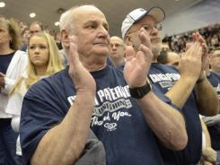 Penn State wrestling fans Gary Reed, left, of Huntingdon, Pa., and George Hoover, right, of Port Matilda, Pa., applaud after a moment of silence in honor of former Penn State football coach Joe Paterno. Third-ranked Penn State swept the last seven matches to hand No. 2 Iowa a 22-12 defeat in front of 6,796 fans at Rec Hall.