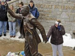 A woman pays her respects at a statue of Joe Paterno outside Beaver Stadium on the Penn State campus after learning of his death Sunday.