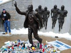 Candles, cards and flowers form a makeshift memorial around the statue of former Penn State coach Joe Paterno outside of Beaver Stadium on the day Paterno died.