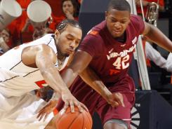 Virginia forward Mike Scott, left, fights for a loose ball with Virginia Tech forward C.J. Barksdale during the first half in Charlottesville, Va.