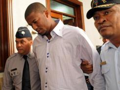 The Indians pitcher known as Fausto Carmona, whose real name is Roberto Hernandez Heredia, is escorted by police out of court in Santo Domingo, Dominican Republic, on Friday.