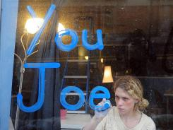 "Robyn Wysk paints ""thank you Joe"" in the window of Surge Business Development in memory of Joe Paterno who died last Sunday."