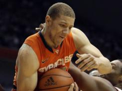 Syracuse guard Brandon Triche pulls a rebound away from Cincinnati forward Yancy Gate during the first half in Cincinnati.