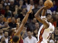The Heat's Chris Bosh (1) shoots over the Cavaliers' Samardo Samuels, left, in the second half of their matchup in Miami. Bosh scored 35 points on 10-of-16 shooting in the Heat's 92-85 win.