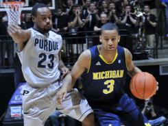 Michigan guard Trey Burke (3) dribbles past Purdue guard Lewis Jackson during their game at Mackey Arena in West Lafayette, Ind.