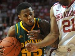 Baylor guard Pierre Jackson (55) handles the ballwhile under pressure from Oklahoma guard Cameron Clark during the first half at the Lloyd Noble Center in Norman, Okla.