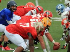 Quarterback Nick Foles and the Senior Bowl's South team offensive line work on plays Tuesday in Mobile, Ala.