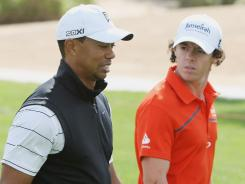 Tiger Woods and Rory McIlroy walk together during a practice round Tuesday ahead of this week's Abu Dhabi HSBC Golf Championship.