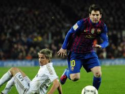 Barcelona's Lionel Messi slips past Real Madrid's Coentrao during their quarterfinal second leg of the Copa del Reyat the Camp Nou in Barcelona.
