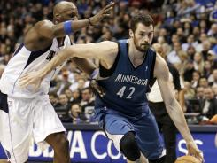 The Timberwolves' Kevin Love (42), seen here driving past the Mavericks' Lamar Odom during their game on Wednesday, had another double-double -- 31 points, 10 rebounds -- on the day he signed a new four-year contract.