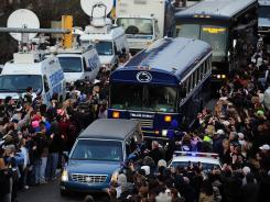 Supports line the road as the hearse caring former Penn State coach Joe Paterno makes a processional in State College after a funeral service Wednesday.