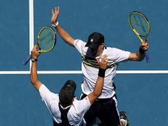 Bob, left, and Mike Bryan of the USA celebrate in their usual style after earning a spot in the doubles final with a victory against Horia Tecau of Romania and Robert Lindstedt of Sweden.