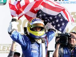 A.J. Allmendinger hoists the American flag after anchoring the Michael Shank Racing quartet to victory in the Daytona Prototype division at the Rolex 24 at Daytona International Speedway.