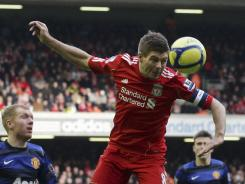 Liverpool's Steven Gerrard, center, heads the ball as Manchester United's Paul Scholes, left, looks on during Liverpool's 2-1 win Saturday.