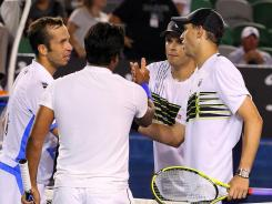 Radek Stepanek of the Czech Republic and Leander Paes of India shake hands at the net with Bob Bryan and Mike Bryan of the USA after winning their mens' doubles title.